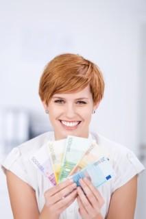 Lachende junge Frau bekommt Kindergeld im Psychologiefernstudium