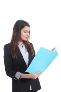 Junge Frau ließt Erfahrungsberichte zum Psychologiefernstudium